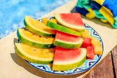 Besnoeiingsplakken en kubussen van rode en gele watermeloen op een gevormde ceramische plaat op de rand van een zwembad Kleurrijk Stock Afbeelding