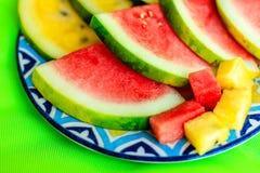 Besnoeiingsplakken en kubussen van rode en gele watermeloen op een kleurrijke gevormde ceramische plaat over heldere kalk groene  Royalty-vrije Stock Afbeeldingen