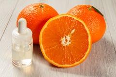 Besnoeiingssinaasappel met twee gehele sinaasappelen en fles met aromatherapy olie op houten raad stock foto