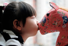 Beso asiático del niño el caballo del juguete Foto de archivo libre de regalías
