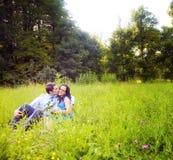Beso de amantes románticos en la hierba verde Foto de archivo