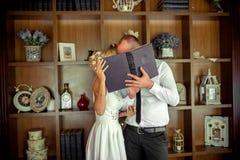 Beso de dos amantes detrás del libro imagen de archivo