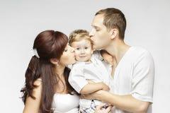 Beso de la familia, padre Kissing Child de la madre, padres y niño foto de archivo