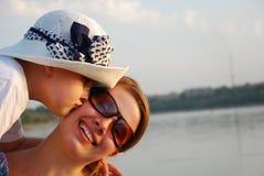 Beso de la hermana en lighti de la puesta del sol imagen de archivo