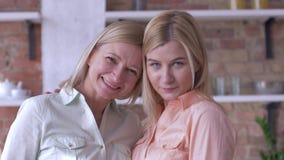 Beso de la madre, retrato de la mamá hermosa de la familia e hija adulta que sonríe y que mira el primer de la cámara metrajes