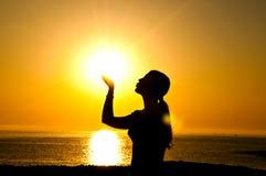 Beso de la silueta de la mujer el sol Imagen de archivo