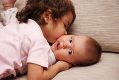 Beso de las hermanas   Foto de archivo