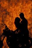 Beso de los pares de la silueta en el fuego de la motocicleta Imagen de archivo