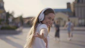 Beso del aire muchacha divertida que camina en la ciudad, madrugada mujer en los auriculares grandes que soplan los besos 4K almacen de metraje de vídeo
