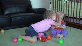 Beso feliz de la hermana su pequeño hermano que juega con las bolas coloridas en casa metrajes