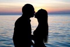 Beso feliz de los pares en la playa Foto de archivo
