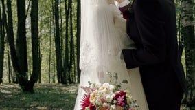 Beso hermoso de la novia y del novio en el bosque almacen de metraje de vídeo