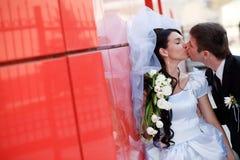 Beso por la pared roja fotos de archivo