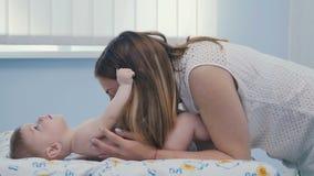 Beso precioso de la madre los fingeres de su pequeño hijo almacen de video