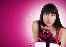 Beso que sopla de la mujer de la Navidad con la caja de regalo y el arco rojo Imágenes de archivo libres de regalías