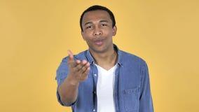 Beso que vuela del hombre africano joven, fondo amarillo almacen de video