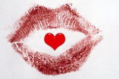 Beso rojo del lápiz labial con un 2.o corazón rojo en el centro Foto de archivo libre de regalías