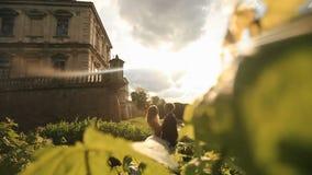 Beso romántico apenas de la pareja casada en parque de la puesta del sol cerca del palacio del Barroco del vintage metrajes