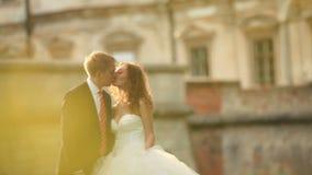 Beso romántico de los pares magníficos del recién casado en parque soleado cerca del palacio del Barroco del vintage metrajes