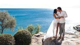 Beso y abrazo de dos amantes en una costa detrás del paisaje marino mediterráneo, tiempo de verano, apenas casado imagen de archivo
