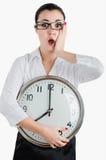 Besorgnis erregende, entsetzte Geschäftsfrau, die eine große Uhr hält Weiße ISO Stockfotografie