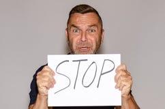 Besorgnis erregender Mann von mittlerem Alter, der ein Stoppschild hält Lizenzfreie Stockfotografie