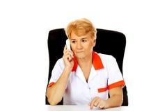 Besorgte ältere Ärztin oder Krankenschwester, die hinter dem Schreibtisch sitzen und durch ein Telefon sprechen Stockbilder