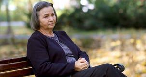Besorgte ältere Frau, die draußen ihre Hände reibt stock footage