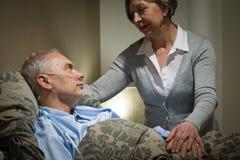 Besorgte ältere Frau, die mit krankem Ehemann sich interessiert Lizenzfreies Stockbild