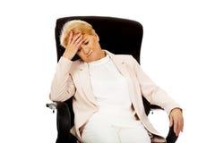 Besorgte ältere Geschäftsfrau, die auf Lehnsessel sitzt Stockfotos