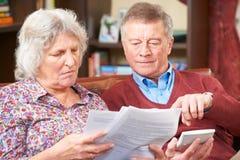 Besorgte ältere Paare, die zusammen Rechnungen betrachten Lizenzfreie Stockfotos