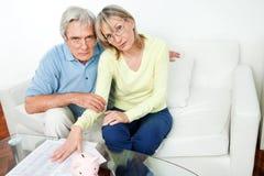 Besorgte ältere Paare mit piggy Lizenzfreie Stockfotografie