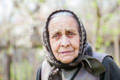 Besorgte alte Dame mit Kopftuch Stockfoto