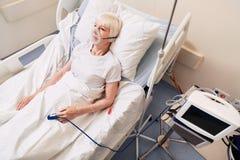 Besorgte alte Dame umgeben durch medizinische Ausrüstung Lizenzfreies Stockfoto