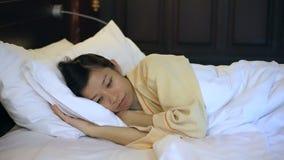 Besorgte asiatische Videofrau im Bett, in der Schlaflosigkeit und im Denken an das Leben stock video