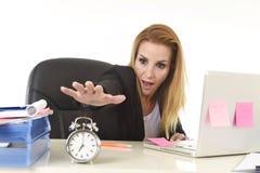 Besorgte attraktive blonde Geschäftsfrau, die weg vom Wecker überwältigt im Druck schaltet Lizenzfreie Stockfotos