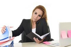 Besorgte beschäftigte attraktive Geschäftsfrau im Druck, der mit Schoss arbeitet stockbilder