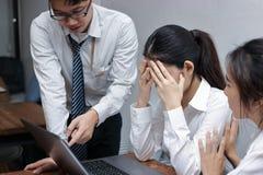 Besorgte deprimierte junge asiatische Geschäftsfrauen werden mit Chef an Arbeitsplatz getadelt Stockbilder