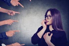 Besorgte Frau beurteilt von den verschiedenen Leuten Stockfotos