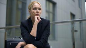 Besorgte Frau, die auf der Bank, besorgt über Entlassung von der Arbeit, Krise sitzt stock video footage