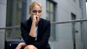 Besorgte Frau, die auf der Bank, besorgt über Entlassung von der Arbeit, Krise sitzt stockbilder