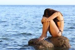 Besorgte Frau, die auf einem Felsen auf dem Strand sitzt stockbilder