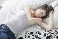 Besorgte Frau, die auf ihrem Bett liegt Stockbild