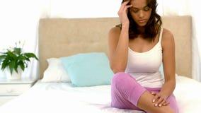 Besorgte Frau, die auf ihrem Bett sitzt stock video footage