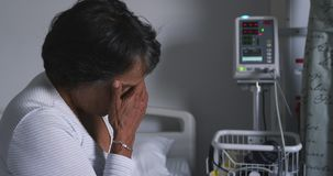 Besorgte Frau, die auf Krankenhausbett 4k sitzt stock footage