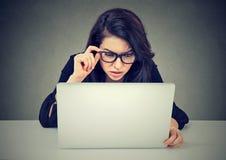 Besorgte Frau, die an dem Laptop betrachtet verwirrt Bildschirm arbeitet lizenzfreie stockfotos