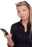 Besorgte Frau, die ihr Mobile betrachtet Stockbilder