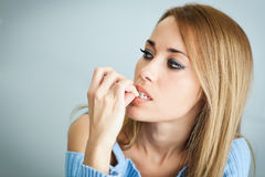 Besorgte Frau, die ihre Nägel beißt Lizenzfreies Stockfoto
