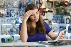 Besorgte Frau, die Rechnungen und Rechnungen im Computer-Shop überprüft Lizenzfreie Stockbilder