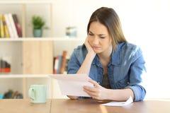 Besorgte Frau, die zu Hause einen Brief auf einer Tabelle liest lizenzfreie stockfotografie